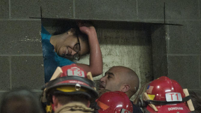 A woman is rescued from being trapped inside a wall of the parking garage at the Gretchen Kafoury Commons in SW Portland, Ore., Wednesday, Jan. 16, 2013. Portland firefighters worked for over three and a half hours cutting her free. (AP Photo/The Oregonian, Brent Wojahn)