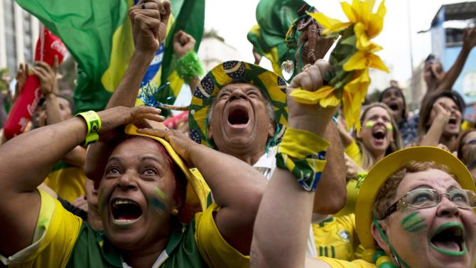 Brazil fans celebrate after their team scored a goal during a penalty shootout after regulation time during the World Cup round of 16 soccer match between Brazil and Chile at the FIFA Fan Fest in Sao Paulo, Brazil, Saturday, June 28, 2014.(AP Photo/Rodrigo Abd)