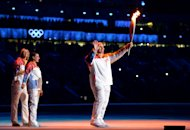 SOCHI, RUSSIA - FEBRUARY 07: Russian former wrestler Alexander Karelin holds up the Olympic torch next to Russian pole vaulter Yelena Isinbayeva (2nd L) and Russian tennis player Maria Sharapova (L) during the opening ceremony of the Sochi 2014 Winter Olympics at the Fisht Olympic Stadium on February 7, 2014, in Sochi, Russia. (Photo by Jung Yeon-Je - Pool/Getty Images)