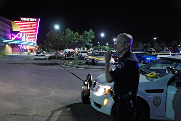 In this July 20, 2012 file photo, an Aurora Police officer talks on his radio outside the Century 16 movie theatre in Aurora, Colo., at the scene of a mass shooting. It wasn&#39;t until more than 20 minutes into the crisis that dispatchers called on the two-person team, but they didnt arrive until more than half an hour after authorities first got word of the shooting. That episode was one of the most glaring examples of ambulance delays that may have cost crucial minutes in the chaotic response to a massacre that ultimately left 12 people dead and dozens wounded. (AP Photo/Ed Andrieski)