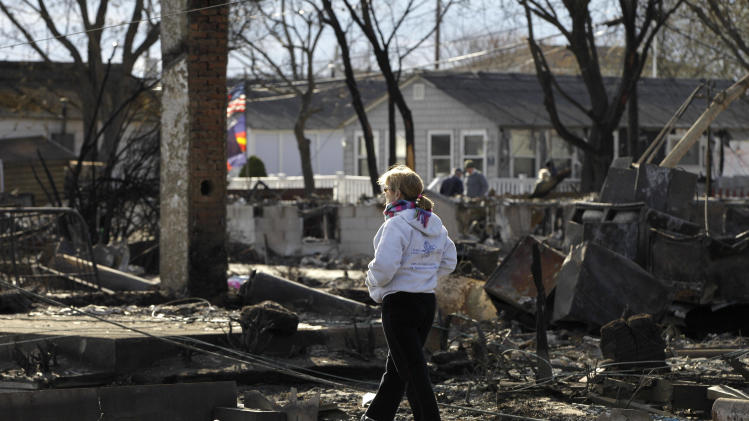 A woman walks through an area impacted by Superstorm Sandy in Breezy Point, Sunday, Nov. 4, 2012, in New York. The beachfront neighborhood heavy populated by firefighters and police officers was devastated during the storm when a fire pushed by Sandy's raging winds destroyed 100 or more homes and buildings. (AP Photo/Kathy Willens)