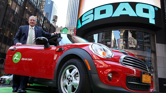 FILE - In this April 14, 2011 file photo provided by Zipcar.com, Zipcar Chairman and CEO Scott Griffith stands with a Zipcar Mini-Cooper before the opening bell at the NASDAQ Market Site in New York. Avis is buying Zipcar for $491.2 million, expanding its offerings from traditional car rentals to car sharing services. The boards of both companies unanimously approved the buyout. (AP Photo/Zipcar.com, Craig Ruttle, File)