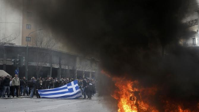 Greek farmers hold a Greek national flag near a burning garbage container during a protest against planned pension reforms outside the Agriculture ministry in Athens
