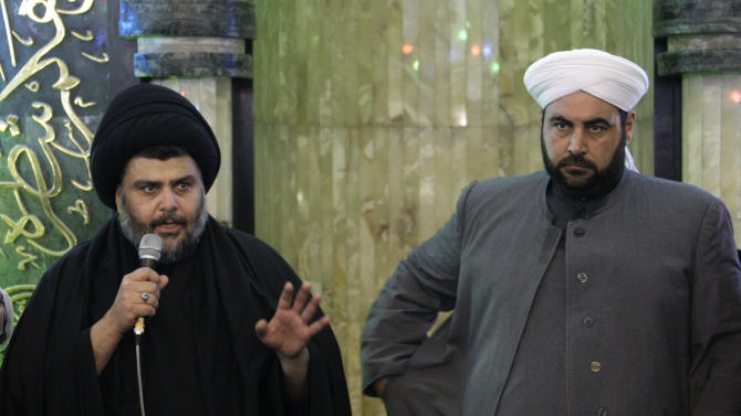 Firebrand Shiite cleric Muqtada al-Sadr, left, address worshippers as a Sunni cleric Anas al-Issawi, right, listens during the Friday prayers at Abdul-Qadir al-Gailani Sunni mosque in Baghdad, Iraq, Friday, Jan. 4, 2013. Al-Sadr paid a visit Friday to a Baghdad church that was the scene of a deadly 2010 attack as well as one of the Iraqi capital's main Sunni mosques, an apparent overture to other religious groups as opposition mounts against his rival, Prime Minister Nouri al-Maliki. (AP Photo/ Khalid Mohammed)
