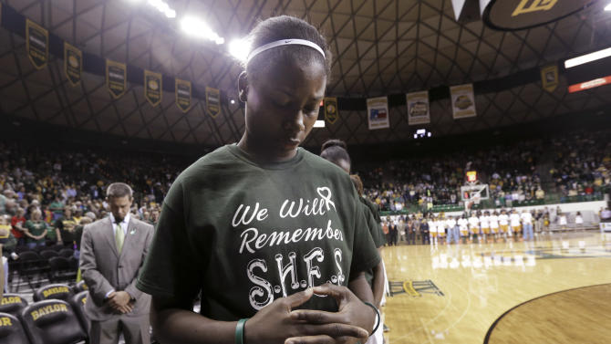 Baylor's Destiny Williams bows her head during a moment of silence for the Sandy Hook Elementary School shooting victims, before an NCAA college basketball game against Tennessee on Tuesday, Dec. 18, 2012, in Waco, Texas. (AP Photo/LM Otero)
