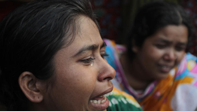 Relatives cry as rescuers look for survivors and victims at the site of a building that collapsed Wednesday in Savar, near Dhaka, Bangladesh,Thursday, April 25, 2013. By Thursday, the death toll reached at least 194 people as rescuers continued to search for injured and missing, after a huge section of an eight-story building that housed several garment factories splintered into a pile of concrete on Wednesday. (AP Photo/A.M.Ahad)