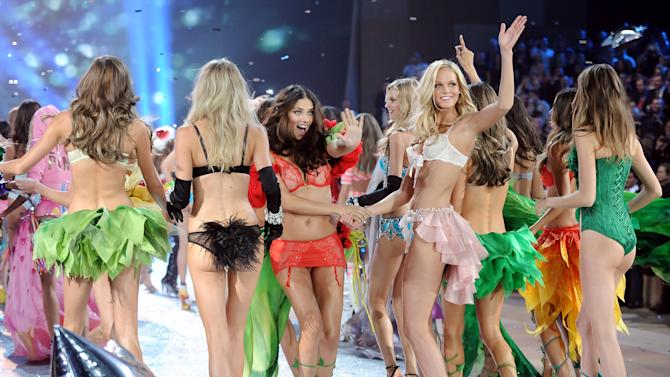 Models Adriana Lima, center, and Erin Heatherton wave during the finale of the 2012 Victoria's Secret Fashion Show on Wednesday Nov. 7, 2012 in New York. The show will be broadcast on Tuesday, Dec. 4 (10:00 PM, ET/PT) on CBS. (Photo by Evan Agostini/Invision/AP)