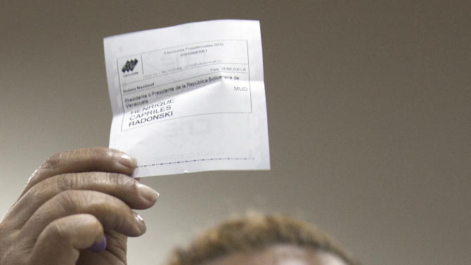 A polling station delegate holds a vote for opposition candidate Henrique Capriles as the counting of votes starts in Caracas, Venezuela, Sunday, April 14, 2013. Venezuelans went to the polls Sunday to choose the next president between Hugo Chavez's chosen successor, ruling party candidate Nicolas Maduro, and opposition candidate Henrique Capriles.(AP Photo/Ramon Espinosa)