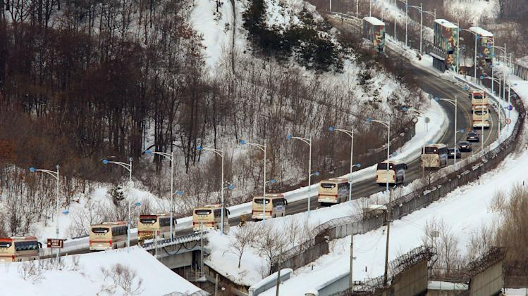 Buses carrying South Koreans cross the border line to Diamond Mountain resort in North Korea, at Goseong, South Korea, Thursday, Feb. 20, 2014. About 500 South Koreans will be reunited with their North Korean relatives at the Diamond Mountain resort in North Korea from Feb. 20 to 25. (AP Photo/Yonhap, Lee Jong-geun) KOREA OUT