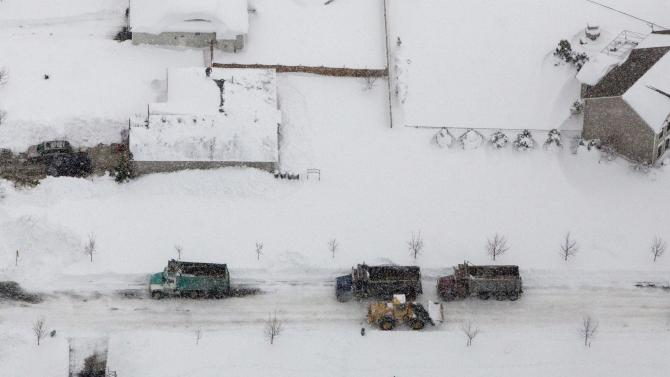 Snow falls on heavy equipment as it is used to clear roads in the town of Cheektowaga near Buffalo, New York