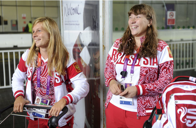 Tatiana Bazyuk and Svetlana Shnitko part of the Russian Olympic sailing squad smile as they wait to board a bus at Heathrow airport, London
