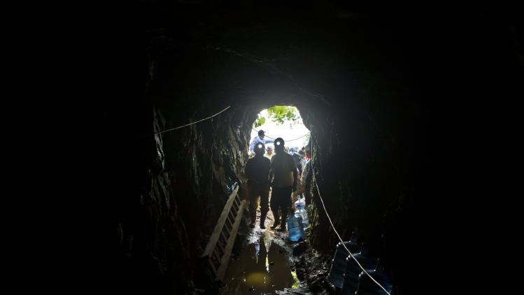 Miners enter the El Comal gold and silver mine to help with rescue operations after a landslide trapped at least 24 miners inside, in Bonanza, Nicaragua, Friday, Aug. 29, 2014. Rescuers on Friday located 20 of at least 24 gold miners trapped by a landslide in northern Nicaragua, but were not immediately able to bring them to safety. (AP Photo/Esteban Felix)