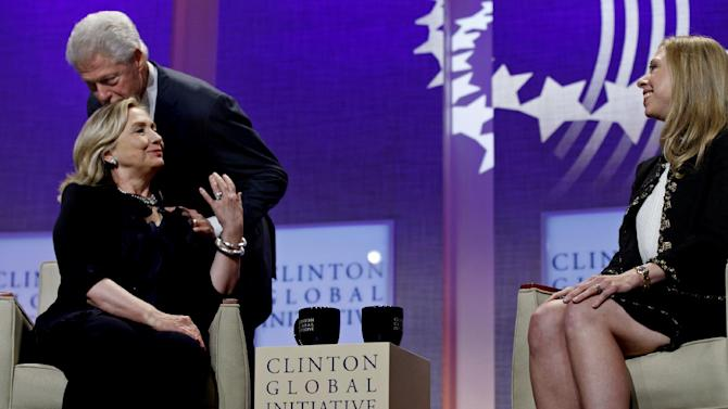 Former President Bill Clinton, Founding Chairman, Clinton Global Initiative, kisses his wife Secretary of State Hillary Rodham Clinton as daughter Chelsea Clinton looks on at the Clinton Global Initiative in New York Thursday, Sept. 22, 2011. (AP Photo/Craig Ruttle)
