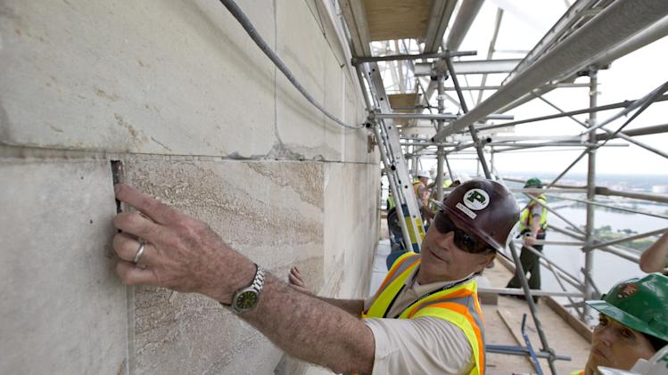 Bob Collie, project manager with Perini Management Services, puts his finger in a crack of the Washington Monument at the 491-foot level of the scaffolding surrounding the monument, Sunday, June 2, 2013 in Washington. The monument has been closed since the 2011 earthquake and half of the needed repairs have been funded by a $7.5 million donation from philanthropist David Rubenstein. The Associated Press had a look at some of the worst damage and the preparations underway to begin making repairs. Stone by stone, engineers are reviewing cracks, missing pieces and broken mortar now that huge scaffolding has been built around the towering symbol of the nation's capital. Once each trouble spot is identified, repairs can begin. (AP Photo/Alex Brandon)