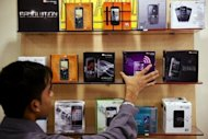 A salesman arranging mobile handsets at a store in New Delhi. India's former telecoms minister A. Raja, who faces trial over a massive corruption case involving mobile telephone licences, was granted bail after 15 months in prison