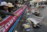 People look at the damage caused by an explosion near Victory Monument in Bangkok January 19, 2014. REUTERS/Paul Barker
