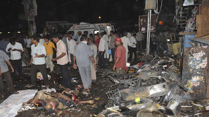 People gather on the scene after a bomb blast in Hyderabad, India,Thursday, Feb.21, 2013. Several people were killed and many injured Thursday in a pair of explosions in a crowded area of the southern Indian city of Hyderabad, officials said. (AP Photo)