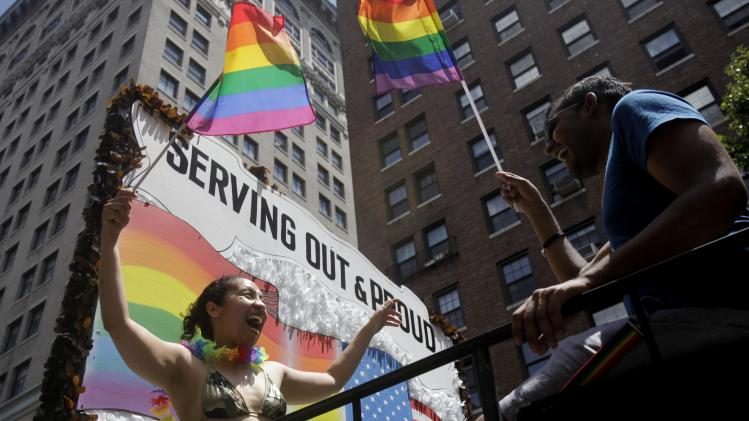 Participants in the Gay Pride Parade laugh and wave flags from a military float in New York, Sunday, June 24, 2012. The parade was held one year to the day of same-sex marriage being legalized in New York state. (AP Photo/Seth Wenig)