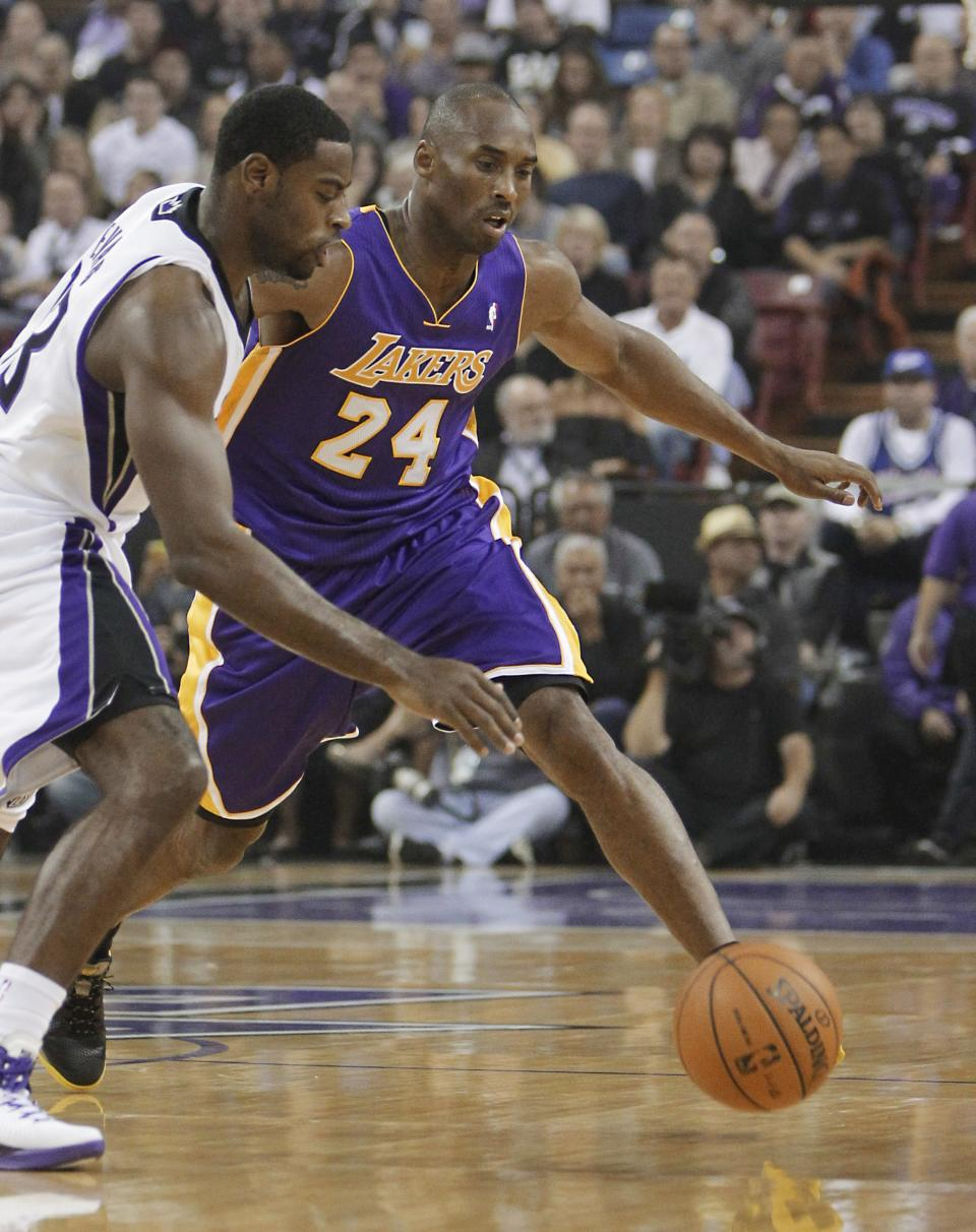 Sacramento Kings guard Tyreke Evans, left, and Los Angeles Lakers guard Kobe Bryant scramble forthe ball during the first quarter of an NBA basketball game in Sacramento, Calif., Wednesday, Nov. 21, 2012. (AP Photo/Rich Pedroncelli)