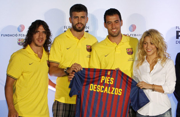 La cantante colombiana Shakira posa con los jugadores del FC Barcelona, de izquierda a derecha, Carles Puyol, Gerard Pique, y Sergio Busquets, en Coral Gables, Florida, el lunes 1 de agosto de 2011. S