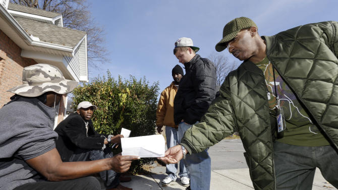 In this Nov. 29, 2012 photo, Kerry Rankins, right, hands a paper to Racinto Lester, left, as a group of former employees of the Veterans Support Organization talk outside the organization's closed office in Nashville, Tenn. The Stuart, Fla.-based Veterans Support Organization had been fined by Tennessee for making false claims about the benefits it offered, and Connecticut lawmakers called for a federal investigation before the group's Tennessee branch closed last month. (AP Photo/Mark Humphrey)