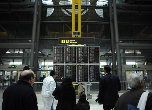 <p>Passengers look at a flight information board at Madrid Barajas airport on December 11, 2011. Spain's debt-struck government says it plans to sell off a stake in airport operator AENA to private investors next year.</p>