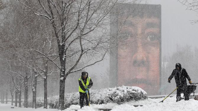 Park workers clear walking paths at Millennium Park Tuesday, March 5, 2013, in downtown Chicago. Chicago was hit Tuesday by a storm expected to dump as much as 10 inches of snow in the area before the end of the day — the most since the 2011 blizzard and its more than 20 inches of snow. (AP Photo/Kiichiro Sato)