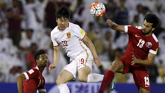 Zheng of China heads the ball next to Afif and Elsayed of Qatar during their 2018 World Cup qualifying soccer match in Doha
