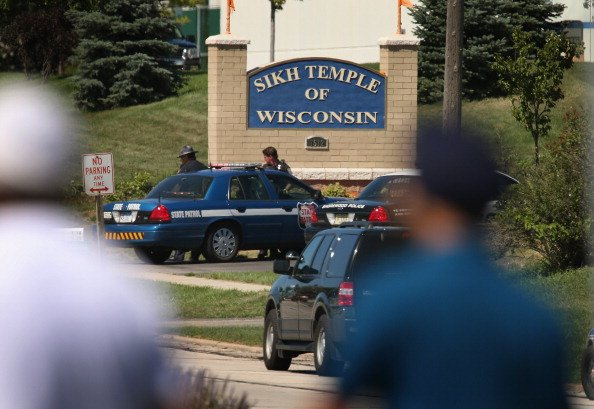 Police guard the front of the Sikh Temple of Wisconsin where at least one gunman fired upon people at a service August, 5, 2012 Oak Creek, Wisconsin. At least six people were killed when a shooter, wh
