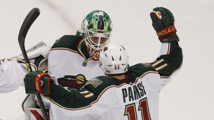Minnesota Wild goalie Niklas Backstrom, back, of Finland, celebrates with left wing Zach Parise after the Wild's 3-1 victory over the Colorado Avalanche in an NHL hockey game in Denver on Saturday, April 27, 2013. With the win, the Wild earned the eighth seed in the NHL Western Conference playoffs. (AP Photo/David Zalubowski)