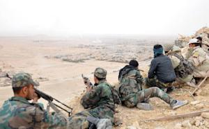 Syrian soldiers overlook the ancient city of Palmyra …