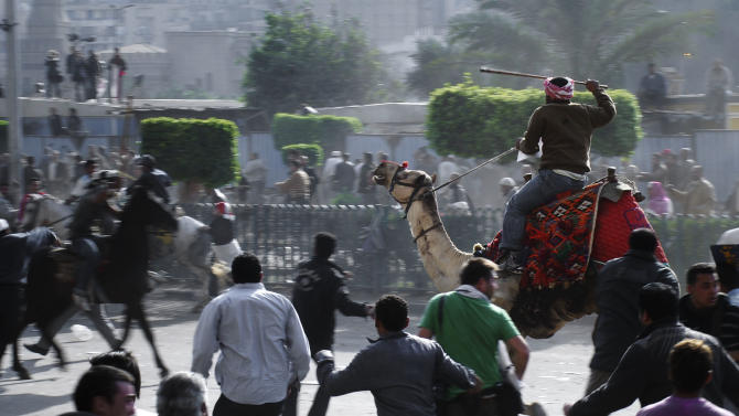 FILE - In this Wednesday, Feb. 2, 2011 file photo, supporters of President Hosni Mubarak, riding camels and horses, fight with anti-Mubarak protesters in Cairo, Egypt. Ousted President Hosni Mubarak watched the uprising against him unfold through a live TV feed, despite his earlier denial that he knew the extent of the protests and violence, according to a fact-finding mission member said Wednesday, Jan. 2, 2013, which could lead to the retrial of the 84-old ousted leader already serving a life sentence.(AP Photo/Mohammed Abu Zaid, File)