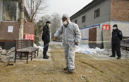 A worker sprays chemicals to disinfect the ground in front of policemen standing guard outside a poultry farm in Baoding