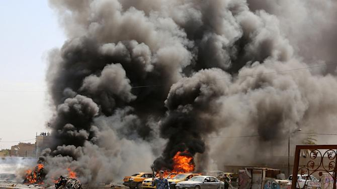 Iraqi policemen stand near burning vehicles moments after one in a series of bombs hit the Shiite stronghold of Sadr City, in Baghdad, Iraq, Tuesday, May 13, 2014. A wave of car bombings in mainly Shiite areas of Baghdad killed tens on Tuesday, officials said. (AP Photo/Karim Kadim)