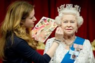 Painter Lisa Burton adds finishing touches to a new waxwork figure of Queen Elizabeth II at Madame Tussauds in London on May 14