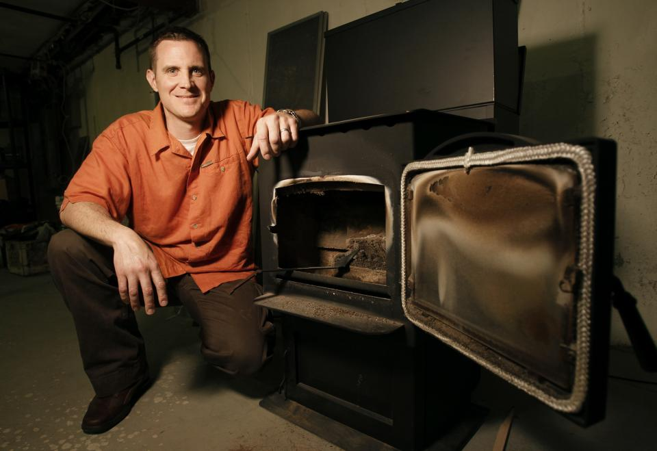CORRECTS SPELLING OF NAME TO BOTELHO, NOT BOTEHLO - In this June 22, 2011 photo Stephen Botelho poses near a pellet burning stove in the basement of his Westwood home. Botelho has installed the stove in the basement as an energy saving measure. (AP Photo/Steven Senne)