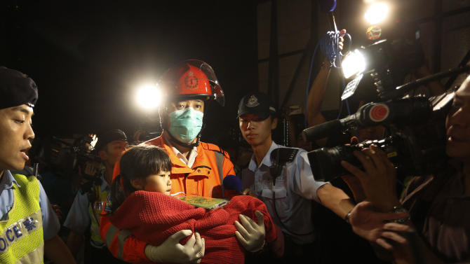A young survivor is carried by a rescuer, and taken onto shore after a collision involving two vessels, in Hong Kong, Tuesday, Oct. 2, 2012. Authorities in Hong Kong have rescued 101 people after a ferry collided with a boat and sank. A local broadcaster says eight people died. The government said in a statement that the ferry was carrying about 120 people when the accident happened Monday night near Lamma Island, off the southwestern coast of Hong Kong Island. Few other details were given. (AP Photo/Vincent Yu)