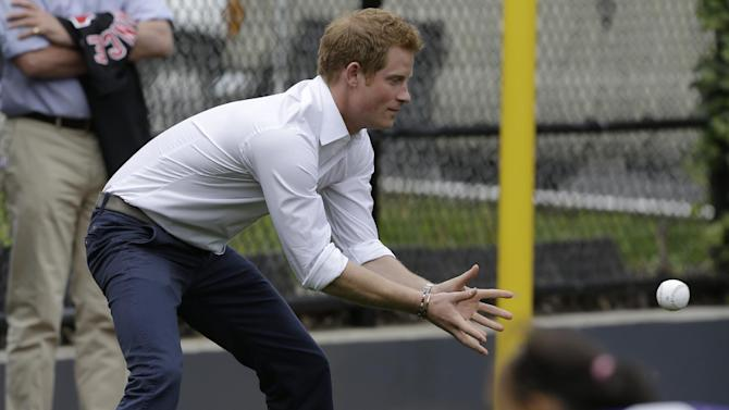 Britain's Prince Harry plays catch with Harlem RBI youngsters during a visit to launch a partnership between the organization and the Royal Foundation of the Duke and Duchess of Cambridge and Prince Harry in New York, Tuesday, May 14, 2013.  (AP Photo/Kathy Willens)