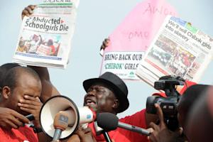 Protesters raise newspapers reporting the deaths of …