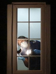 <p>A British police crime scene investigator examines the interior of a window inside the home of a family shot dead in their car in the French Alps in Claygate, in south-east England, on September 8. The four-year-old girl who survived the execution-style killing of her family in the French Alps was due to return to Britain as police again quizzed relatives and scoured the family home.</p>