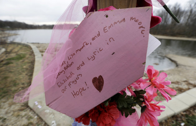A sign sits attached to a memorial near Meyers Lake where cousins Lyric Cook, 10, and Elizabeth Collins, 8, disappeared in July while riding their bikes, Thursday, Dec. 6, 2012, in Evansdale, Iowa. Fa