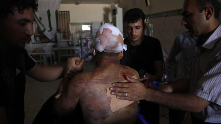 Palestinian refugee Mohammed, second name not given,  21, receives treatment in a field hospital after he was found with three gunshot wounds in town of Anadan on the outskirts of Aleppo, Syria, Monday, Aug. 6, 2012. (AP Photo)