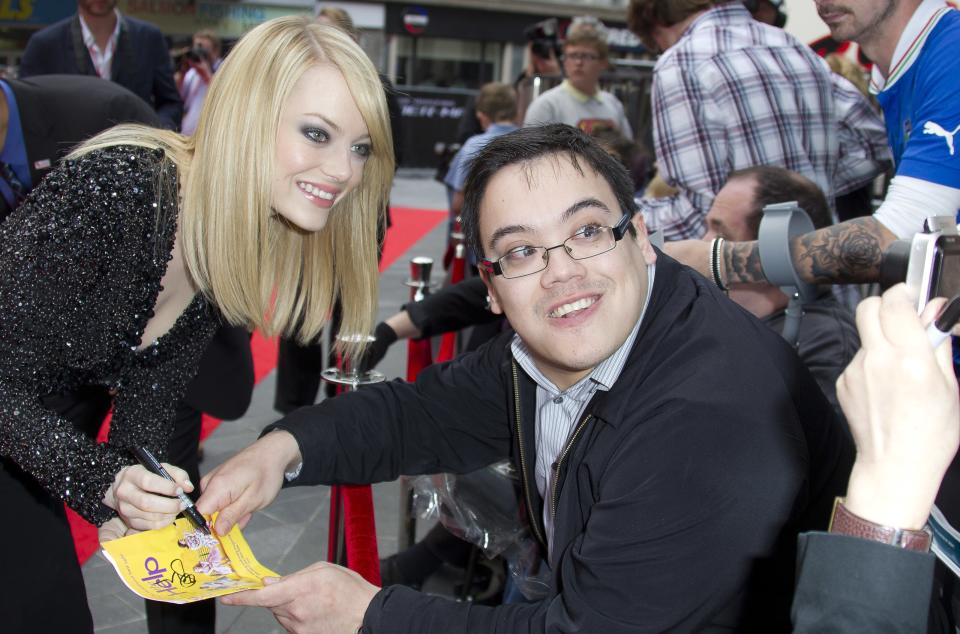 US actress Emma Stone signs autographs for fans as she arrives for the UK premiere of The Amazing Spider-Man at a central London cinema, Monday, June 18, 2012. (AP Photo/Joel Ryan)