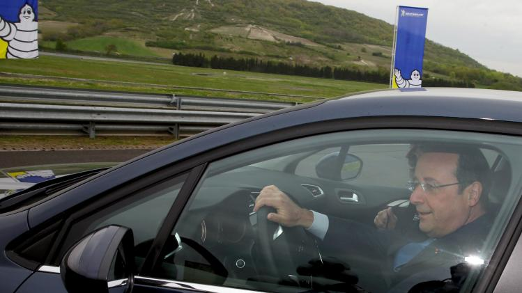 French President Hollande drives a car to test tyres at Michelin factory