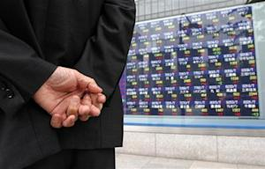 A man looks at a stock index board outside a brokerage in Tokyo