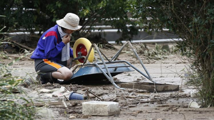 A woman kneels next to a wheelbarrow at a site where a landslide swept through a residential area at Asaminami ward in Hiroshima