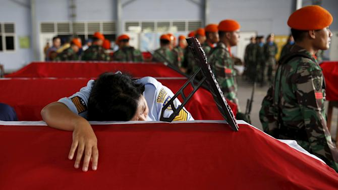 Swet Eka, an Indonesian soldier, mourns on the coffin of her husband, a victim in an Indonesian military C-130 Hercules transport plane that crashed into residential area, inside military airbase in Medan