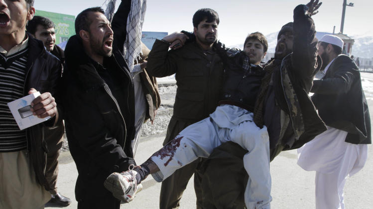 Afghans carry a wounded man during  anti-U.S. protest  in Kabul, Afghanistan, Friday, Feb. 24, 2012. Thousands of Afghans staged new demonstrations Friday over the burning of Qurans at a U.S. military base in Afghanistan. (AP Photo/Musadeq Sadeq)