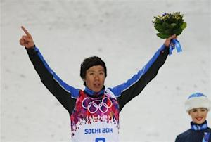 China's third placed Jia celebrates on podium after the men's freestyle skiing aerials finals at the 2014 Sochi Winter Olympic Games in Rosa Khutor