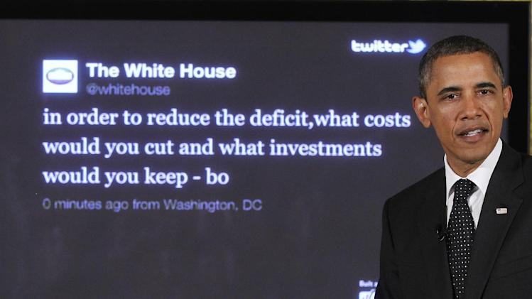 """FILE - In this July 6, 2011, file photo, President Barack Obama sits in front of a screen displaying a question he tweeted during a """"Twitter Town Hall"""" in the East Room of the White House in Washington. President Obama is introducing a new hashtag to the fiscal cliff debate. The White House plans to promote (hashtag)My2K on Twitter and other social media — a reference to the estimated $2,200 tax increase that a typical middle-class family of four would see if the Bush tax cuts expire. (AP Photo/Charles Dharapak, File)"""